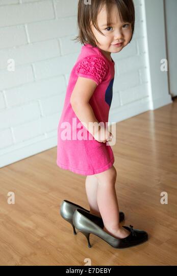 Babymädchen in ihrer Mutter Schuhe Stockbild