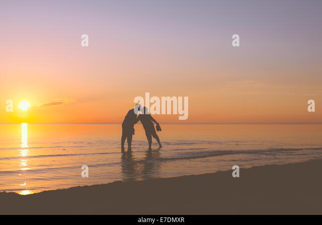 Älteres Paar küssen bei Sonnenuntergang Stockbild