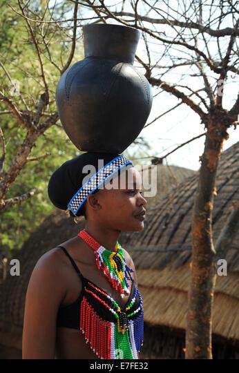 Szene von Zulu Maiden im bunten Kleid balancieren schwarzen Tontopf auf Kopf im Kulturdorf Shakaland Südafrika Stockbild