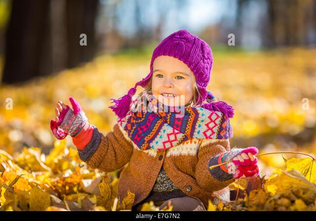Kleine Mädchen spielen mit Herbstlaub Stockbild