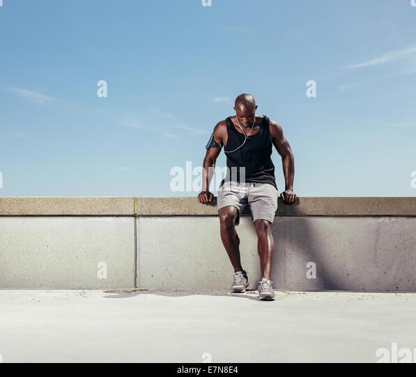 Muskulösen jungen Mann Atem nach seinen Lauf nehmen. Afrikanische Sportler im Freien mit Textfreiraum. Entspannen Stockbild