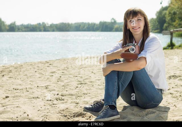 Lächelnde Hipster Frau posiert mit alten Film-Kamera am Strand im Sommer mittags. Urlaub-Hintergrund Stockbild