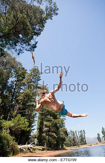 Mann springt in ländlichen See Stockbild
