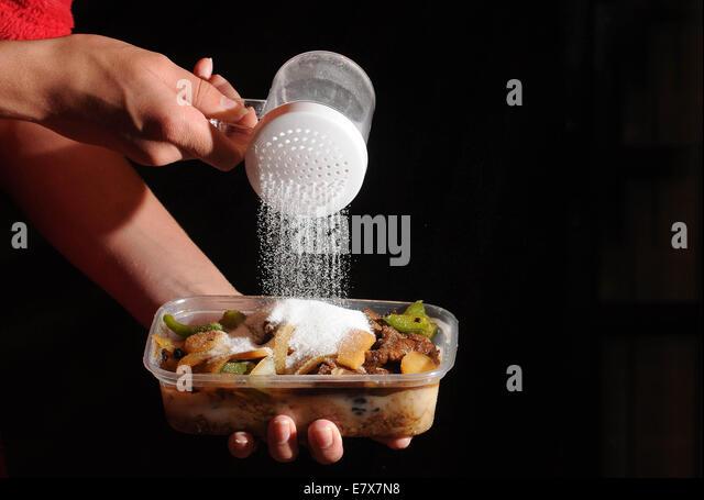 Speisen zum Mitnehmen mit Salz auf von oben gegossen wird. Hohe Niveaus des Salzes in Junk-Food verursachen, Bluthochdruck Stockbild