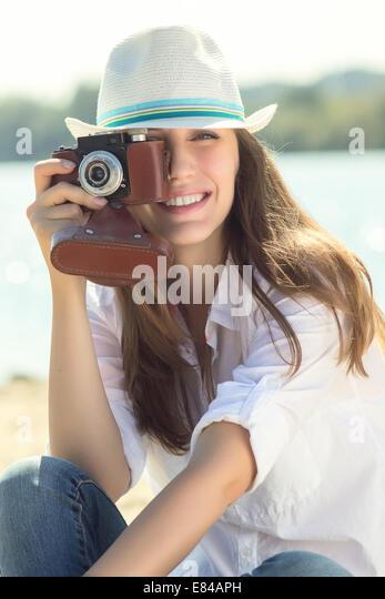 Lächelnde Frau mit Hipster mit alten Kamera am Strand. Kaukasische Mädchen im Urlaub Stockbild