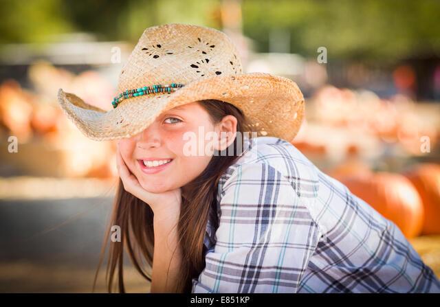 Ziemlich Preteen Mädchen tragen Cowboyhut Porträt im Kürbisbeet in rustikaler Umgebung. Stockbild