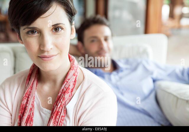 Frau sitzt im Wohnzimmer mit Mann im Hintergrund, Porträt Stockbild