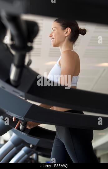 Frau am Trainingsgerät in Turnhalle Stockbild