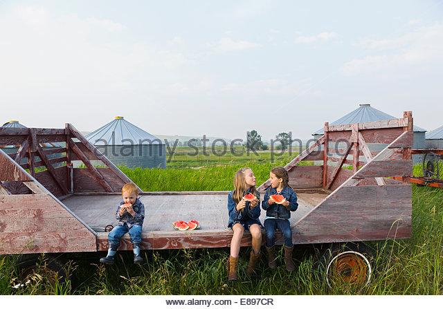 Mädchen und jungen Essen Wassermelone auf Bauernhof Stockbild
