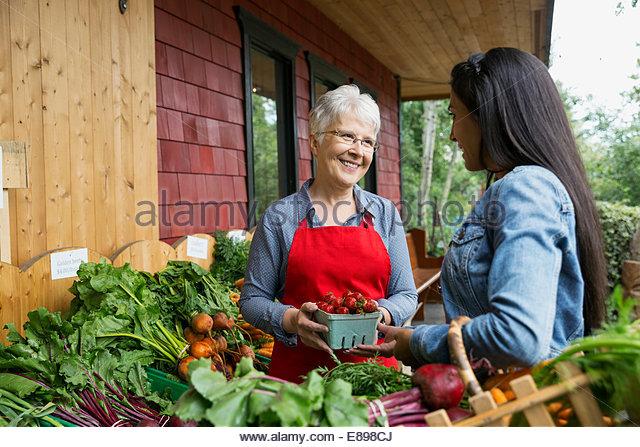 Arbeiter helfen Frau mit außen Gemüsemarkt Stockbild