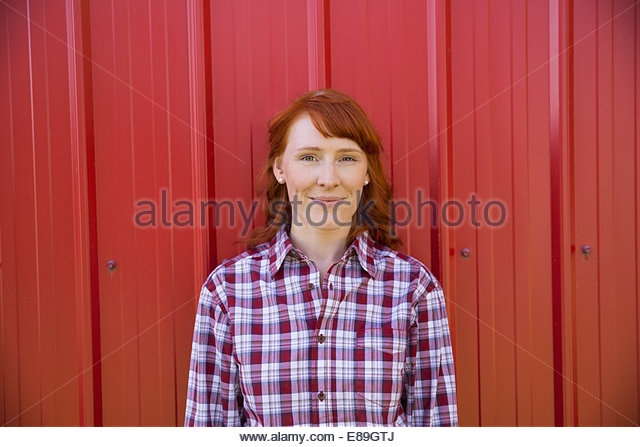 Porträt der lächelnde Frau gegen rote Wand Stockbild