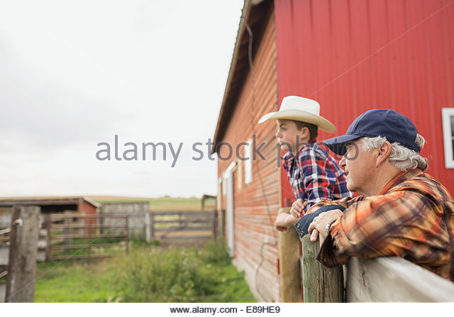 Großvater und Enkel stützte sich auf Zaun auf Bauernhof Stockbild