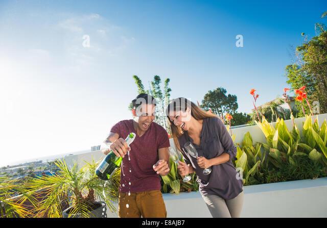 Paar Eröffnung Champagner in Penthouse-Dachgarten, La Jolla, Kalifornien, USA Stockbild
