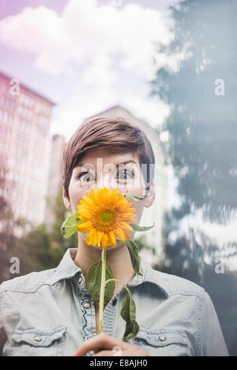 Frau Deckung Mund mit Blume Stockbild