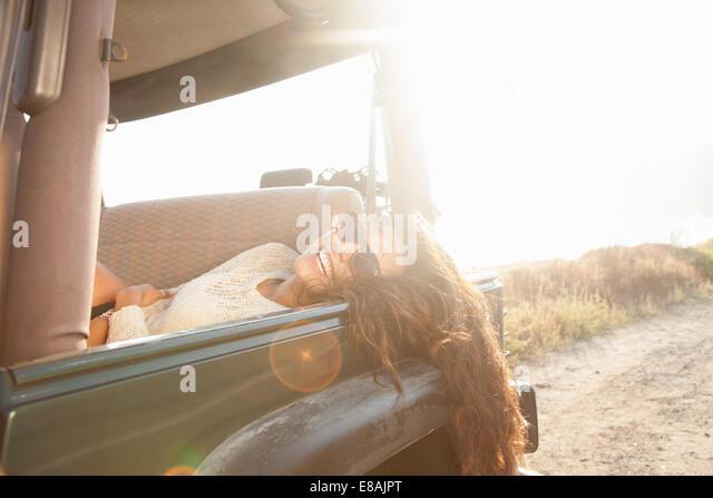 Porträt der jungen Frau liegend auf der Rückseite Sitz des Jeep an Küste, Malibu, Kalifornien, USA Stockbild