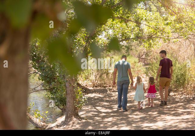 Rückansicht des männlichen Partner mit zwei Töchtern im Park spazieren Stockbild
