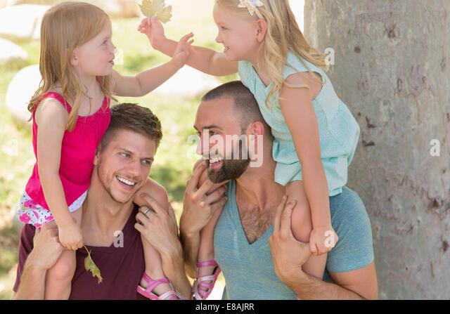 Zwei Schwestern sitzen auf den Schultern der Väter im park Stockbild
