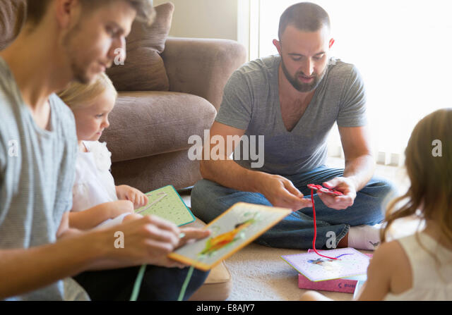 Männlichen Partner und zwei Töchter Einfädeln Bilderbücher Erdgeschoss Wohnzimmer Stockbild