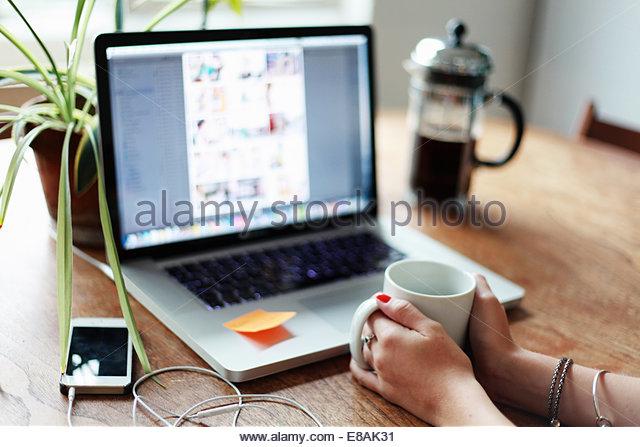 Person, die Becher mit Laptop im Hintergrund Stockbild