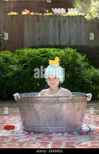 Porträt eines Mädchens im Schaumbad im Garten mit Gummiente auf Kopf Stockbild