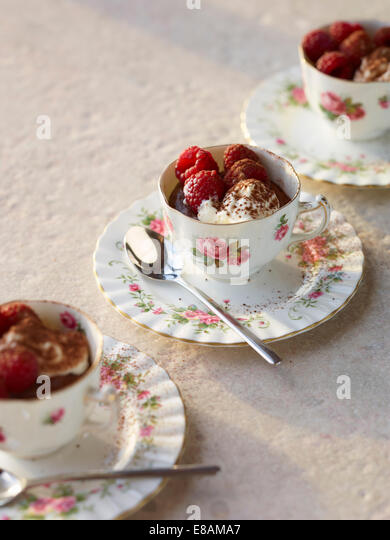 Schokoladenmousse mit Himbeeren und Sahne in Vintage Teetassen Stockbild
