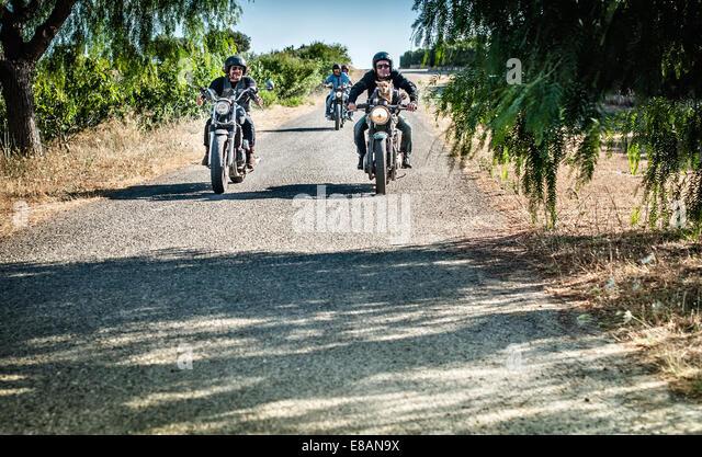 Vier Freunde und ein Hund Motorradfahren auf Landstraße, Cagliari, Sardinien, Italien Stockbild