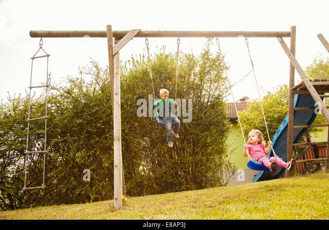 Bruder und Schwester spielen auf Schaukeln im Garten Stockbild