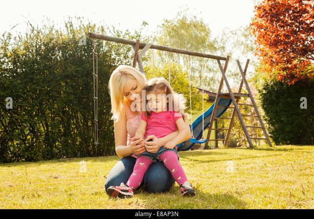 Mutter und Tochter im Garten Schaukeln im Hintergrund Stockbild