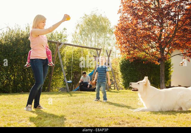 Familie im Garten Ausbildung Hund Stockbild