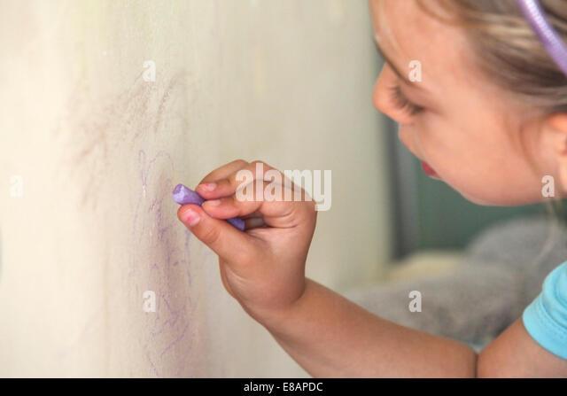 Junges Mädchen auf Wand mit Kreide zeichnen Stockbild