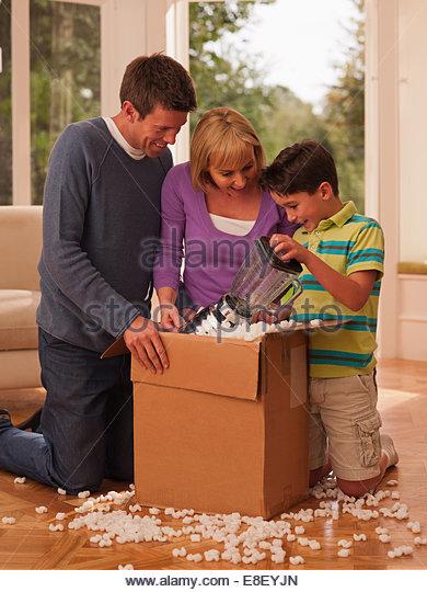 Familie Öffnung Box im Wohnzimmer Stockbild