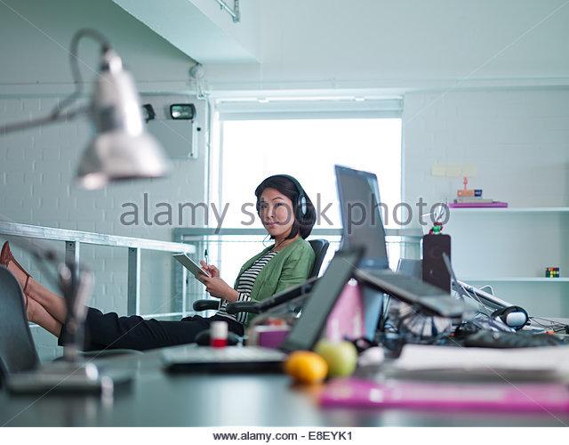 Geschäftsfrau mit Kopfhörern schreiben auf Notizen im Büro Stockbild