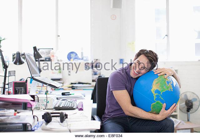 Lächelnd Geschäftsmann umarmt Globus am Schreibtisch im Büro Stockbild