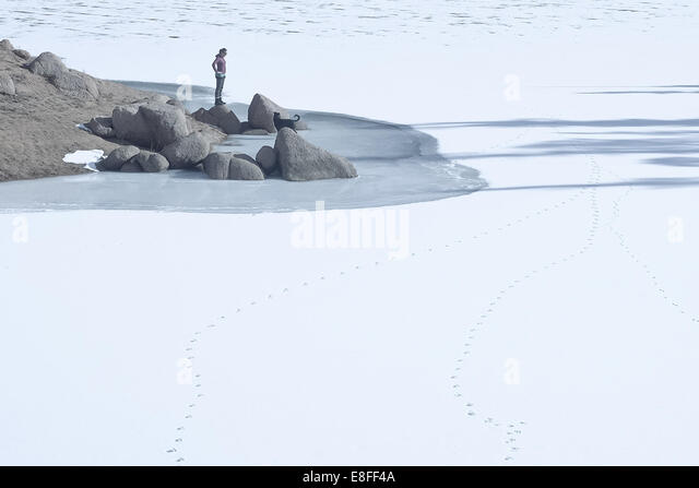 Frau mit Hund tatenlos zugefrorenen See, Colorado, America, USA Stockbild
