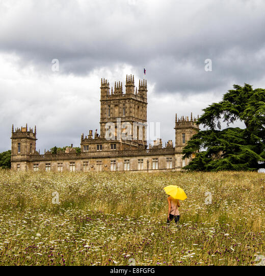 UK, Hampshire, Highclere Castle, Frau mit gelben Regenschirm auf Wiese Stockbild