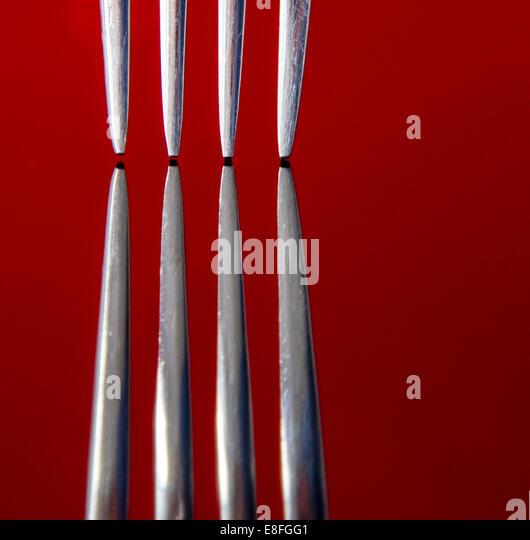 Nahaufnahme von Gabel Zacken am roten reflektierenden Oberfläche, Studio gedreht Stockbild