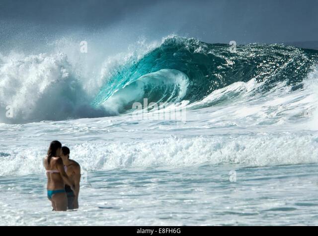 Menschen stehen im Ozean und riesige Meereswelle im Hintergrund Stockbild