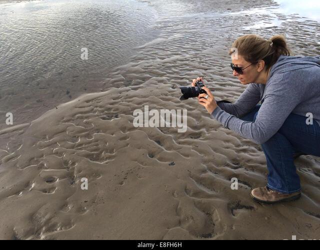 Frau mit dem Fotografieren am Strand, Wales, Großbritannien Stockbild