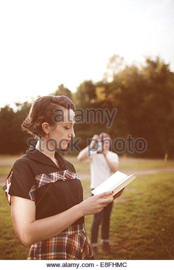 Junger Mann nehmen Foto von Frau liest Buch Stockbild
