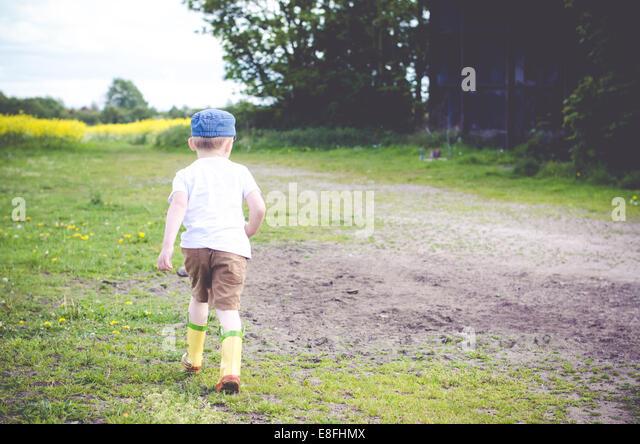 Junge im ländlichen Landschaft laufen Stockbild
