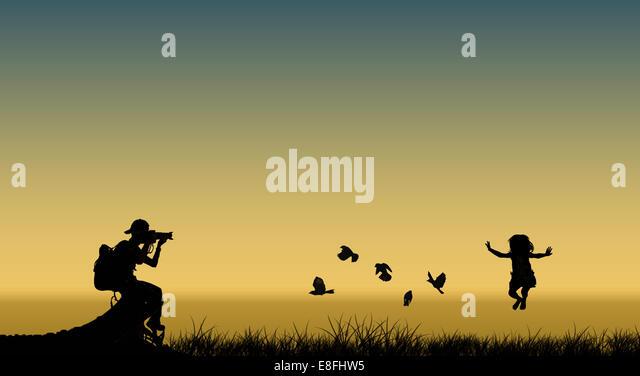 Silhouette der Fotograf unter Bild des springenden Mädchen und fliegende Vögel Stockbild