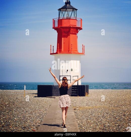 Frau stand vor Leuchtturm Stockbild