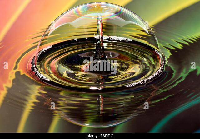 Wassertropfen auf Blase mit Regenbogen-Hintergrund Stockbild