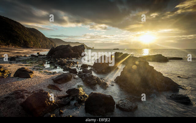 Japan, Okinawa, Sonnenaufgang über dem Meer und Felsen Stockbild