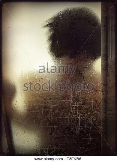 Frau am Fenster gelehnt Stockbild