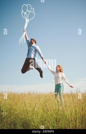USA, Tennessee, Davidson County, Nashville, paar mit abstrakten Luftballons auf Wiese Stockbild
