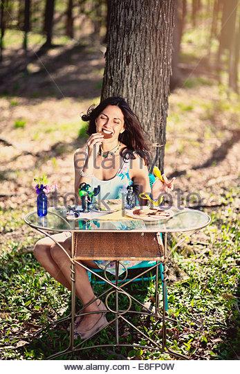 Junge Frau Essen Cookie im Wald Stockbild