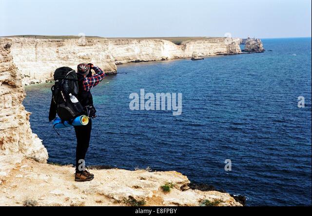 Wanderer am Rand der Klippe fotografieren des Meeres, Rückansicht Stockbild