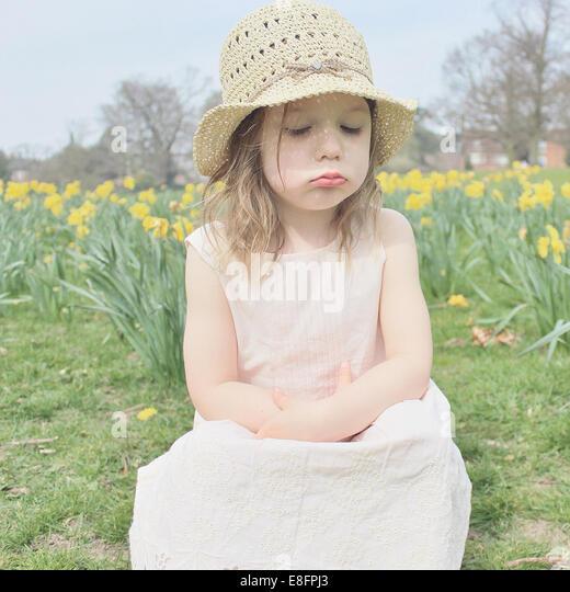 Mädchen sitzen in einem Feld schmollen Stockbild