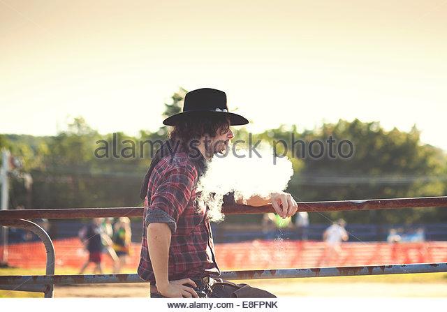 Cowboy auf Zaun gelehnt und Rauch Ausatmen Stockbild